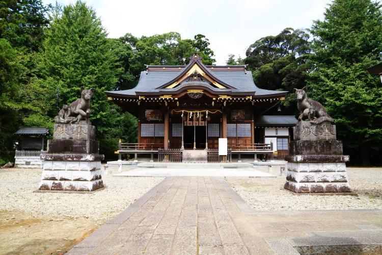 親子ギツネの石像と女化神社の社殿