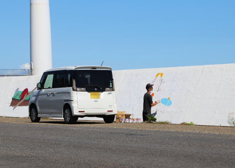 護岸壁に絵を描いている男性