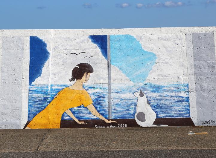 猫と海を眺める女性