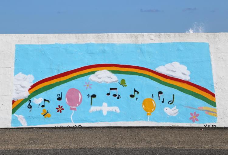 虹を背景に歌う仲間