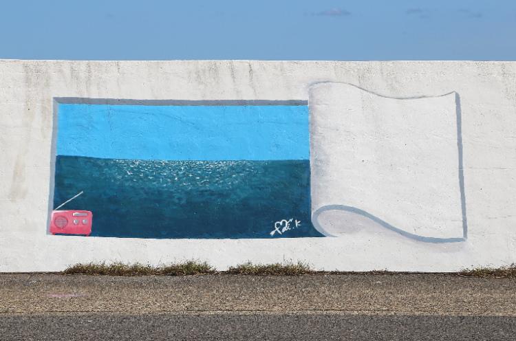 めくれた護岸壁と海