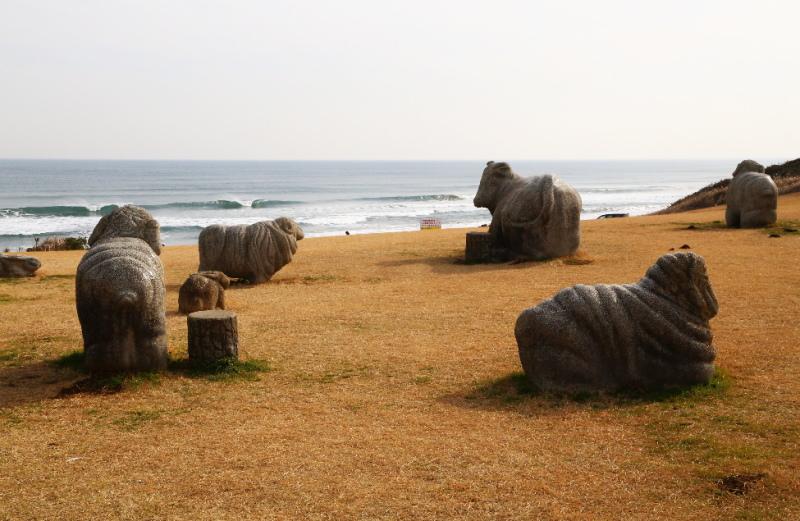 石の牛や羊と一緒に海を眺める