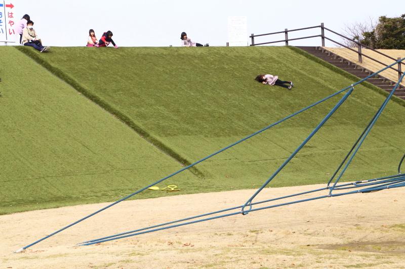 鹿島灘海浜公園の人口すべり台を逆に降りて行く子ども